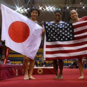 Mai Murakami (left), Simone Biles (center) and Morgan Hurd (right) pose with their flags after taking the women's all-around medals at the 2018 Worlds
