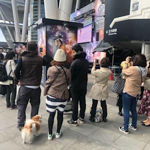 Fans taking photos of a Yuzuru Hanyu poster at the World Figure Skating Championships