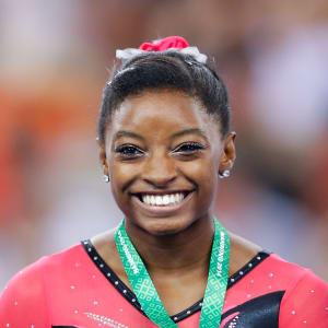 Simone Biles smiles with her floor exercise gold medal at the 2014 Worlds