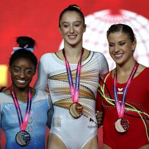 Simone Biles (left), Nina Derwael (center) and Elisabeth Seitz (right) share the uneven bars podium at the 2018 Worlds