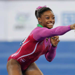 Simone Biles swats away a bee during awards at the 2014 Worlds