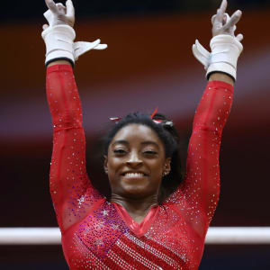 Simone Biles smiles after dismounting the uneven bars during the team final at the 2018 Worlds