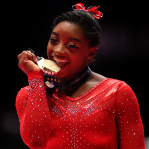 Simone Biles bites her medal after winning the 2015 World all-around title