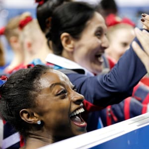 Simone Biles smiles after winning team gold in 2014
