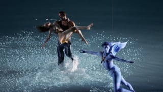 Two performers dance as a performer representing Eros, Archer of Love, from Greek mythology flies overhead during the opening ceremony of the Athens 2004 Summer Olympic Games.