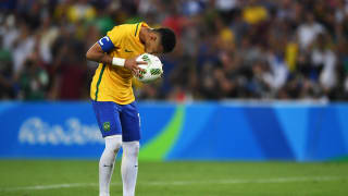 Neymar of Brazil kisses the ball as he prepares to take the winning penalty in the penalty shoot out during the Men's Football Final between Brazil and Germany at the Maracana Stadium.