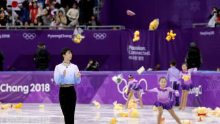 Fans throw gifts on to the ice and hold Japanese flags for Yuzuru Hanyu after his routine during the 2018 PyeongChang Winter Olympic Games.