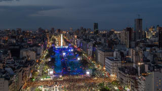 Aerial view of the Avenida 9 de Julio and the Obelisk of Buenos Aires as night starts to fall over the huge crowds filling the streets at the start of the Opening Ceremony.