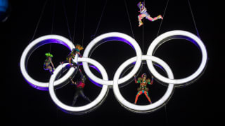 Acrobats, dressed as labourers, 'building' the Olympic Rings in the air during the Opening Ceremony.