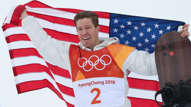 Shaun White holds up the USA flag and his snowboard in celebration of winning the gold medal.
