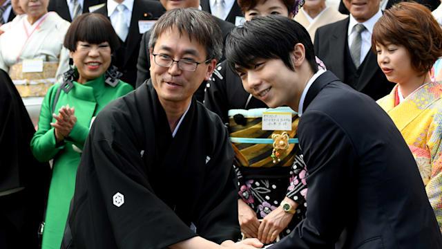 Yuzuru Hanyu shakes hands with Shogi champion Yoshiharu Habu