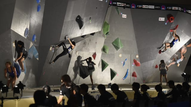 A wide-angle shot of an inverted climbing wall with a dark grey surface and large green, blue and red holds.