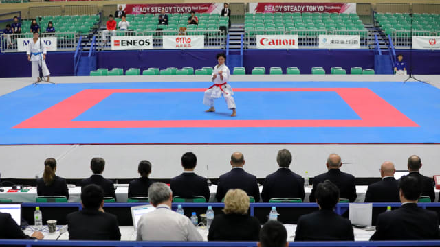 Athlete performs kata in front of the judges