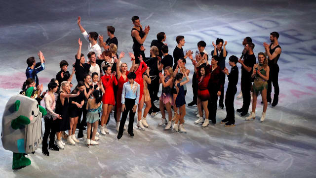 The skaters and stadium mascot Tamarlin thank the audience after the exhibition gala. (REUTERS/Issei Kato)