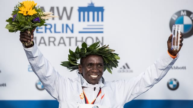 Eliud Kipchoge celebrates on the podium after winning the 2018 Berlin marathon