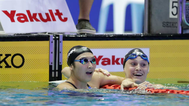 Rikako Ikee celebrates 100m butterfly victory at the 2018 Pan Pacific Championships with runner-up Kelsi Dahlia
