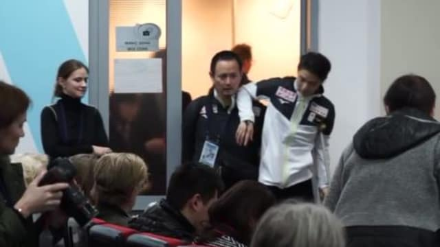 Yuzuru Hanyu, using a crutch, is helped into the Rostelecom Cup press conference