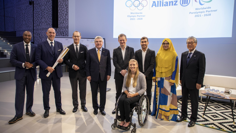 Dignitaries from Allianz, the IOC, and the IPC, posing alongside Olympians and Paralympians at the announcement of Allianz signing on as a Worldwide TOP Partner.