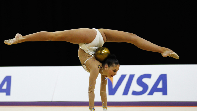 Gymnast Daria Kondakova balances a golden ball in the curve of her back as she performs a handstand with her legs split in a horizontal position.