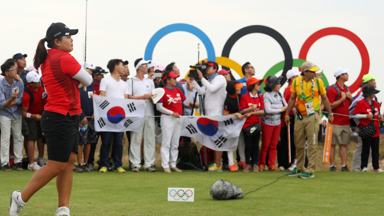 A female golfer watches her tee-off as the audience looks on at the start of a golf hole.