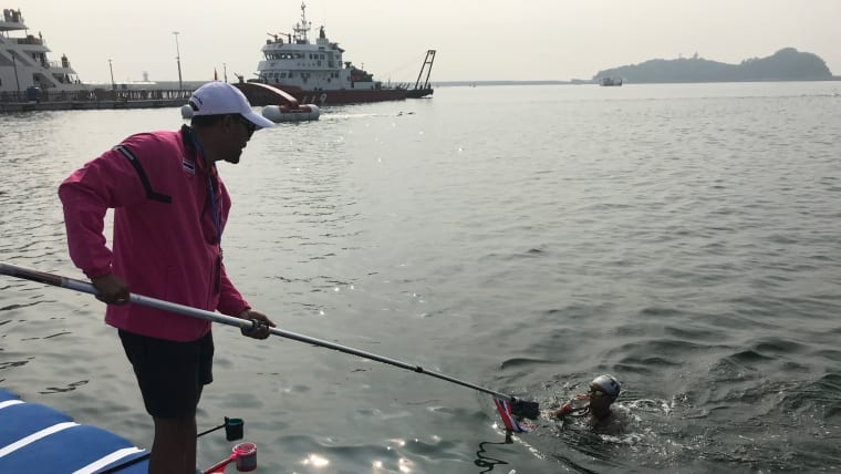 A coach provides nourishment to their swimmer at the Yeosu Ocean Park open water swimming venue