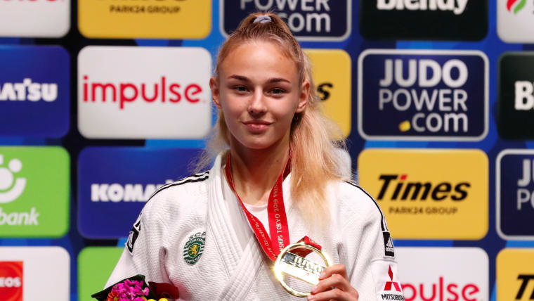 Daria Bilodid poses with her gold medal on the podium.