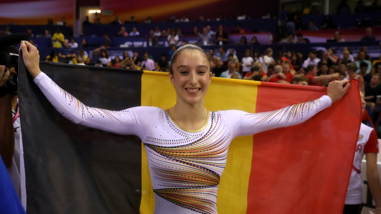 Nina Derwael poses with the Belgian flag after winning the world uneven bars title