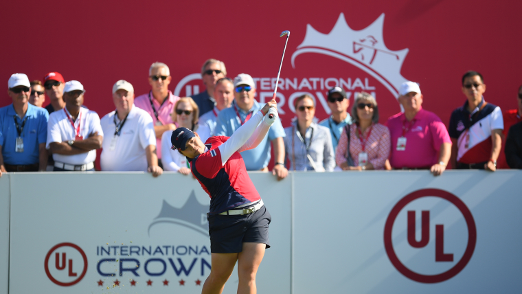 A female golfer standing at the tee after taking a shot while the crowd looks on.