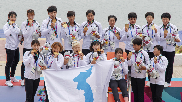 The unified Korean women's dragon boat team pose with their Asian Games gold medals after winning the 500m