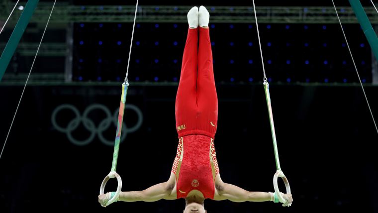 Gymnast Yang Liu holds his body upside down in a cross shape with his legs pointing up and his arms stretched out horizontally holding the rings.