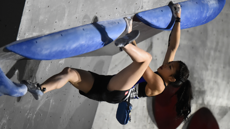 Climber Miho Nonaka holds on to a steep, inclined face of a climbing wall using the blue hand and feet holds.
