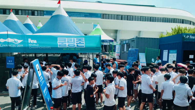 Local school kids cool off outside the Yeomju Gymnasium with an ice-pop