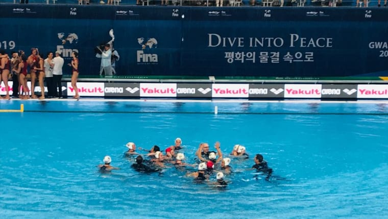 Team USA - players and coaches - celebrate together in the water