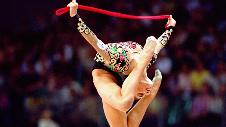 Gymnast Aline Kavaeva performs a jump with her legs bent upwards, her feet pointing up and her back bent towards the floor .