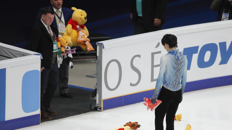 Coaches Brian Orser (L) and Ghislain Briand await Yuzuru Hanyu after his world record short program at the Rostelecom Cup