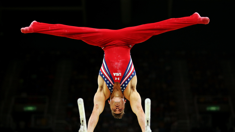 Gymnast Samuel Mikulak performs a handstand on the parallel bars with his legs split into a horizontal position.