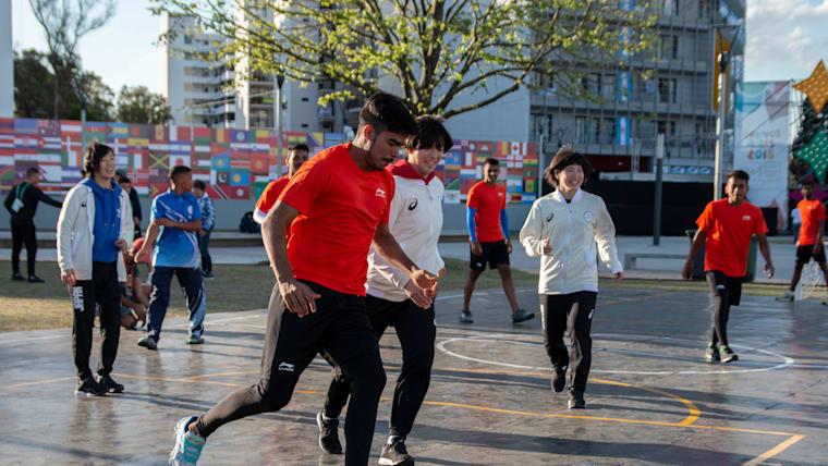 選手村において他国の選手たちとサッカーを楽しむ日本人選手たち