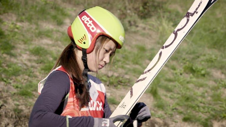 Zhai Yujia looks at skis at ski jump in Norway
