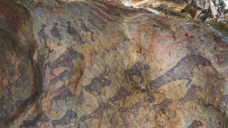 An ancient painting in a cave show rows of figures standing on what look like skis (top L), with herds of animals running below them, on the outskirts of Altay.