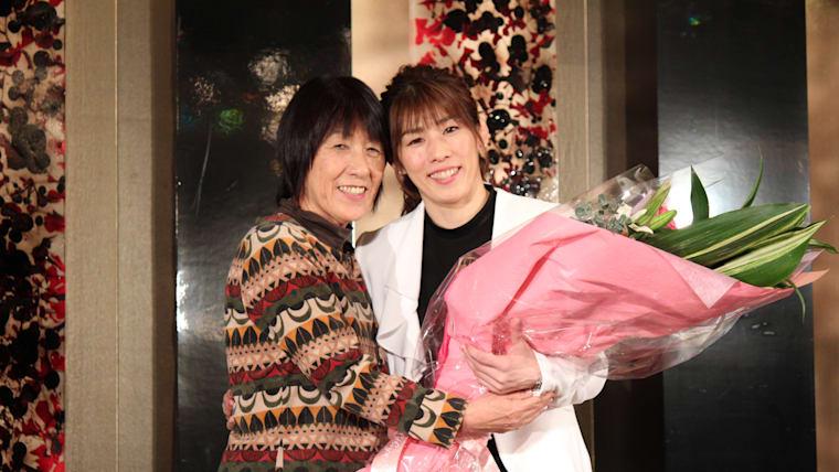 母・幸代さん(左)から花束を受け取る吉田沙保里さん(右)。