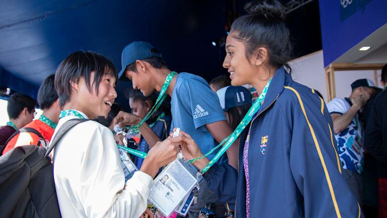 スリランカの選手とメモリーカードを使って情報交換をする陸上の女子代表・金光由樹選手
