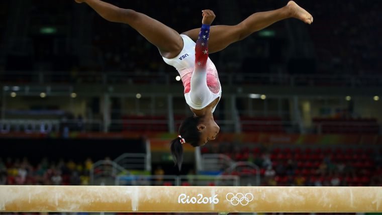 Simone Biles performs a flip on the balance beam at the Rio Olympic Games 2016.