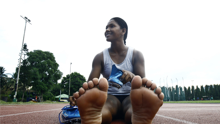 India's Swapna Barman prepares to wear her track shoes before a training session. She won Heptathlon gold at the Asian Games.