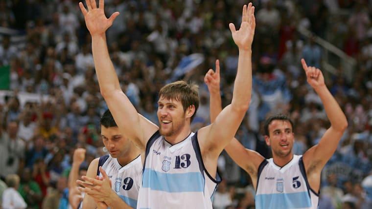 Gabriel Diego Fernández, Andrés Nocioni y Emanuel Ginóbili de Argentina celebran la derrota de Estados Unidos en el partido semifinal de baloncesto masculino en los Juegos Olímpicos de Atenas 2004. (Foto por Chris McGrath / Getty Images)