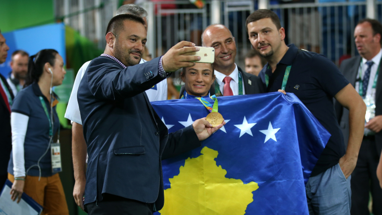 Driton Kuka holds Majlinda Kelmendi's gold medal as he takes a selfie with the Kosovan flag at Rio 2016