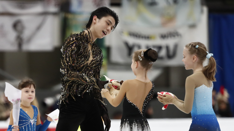 Yuzuru Hanyu receives gifts from children after his free skate at the Rostelecom Cup