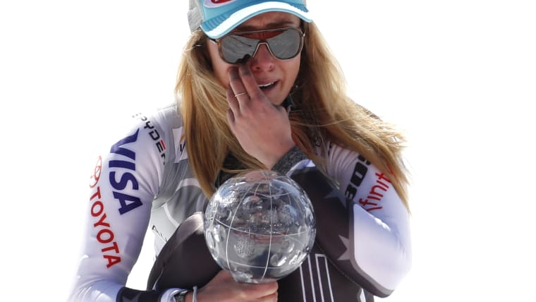 Mikaela Shiffrin struggles to contain her emotions as she crouches on the podium with her giant slalom crystal globe