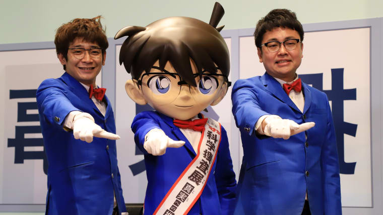 Japanese comedy duo Ginshari pose with a Detective Conan doll at the 'Detective Conan Science Investigation' exhibition in Tokyo in April 2018