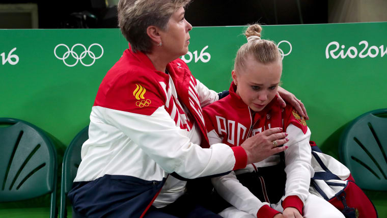 Angelina Melnikova is consoled by her coach after failing to reach the all-around final at Rio 2016