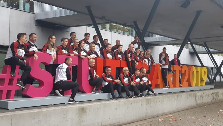 Germany's gymnastics teams pose with the Stuttgart 2019 sign outside the Hanns-Martin-Schleyer-Halle